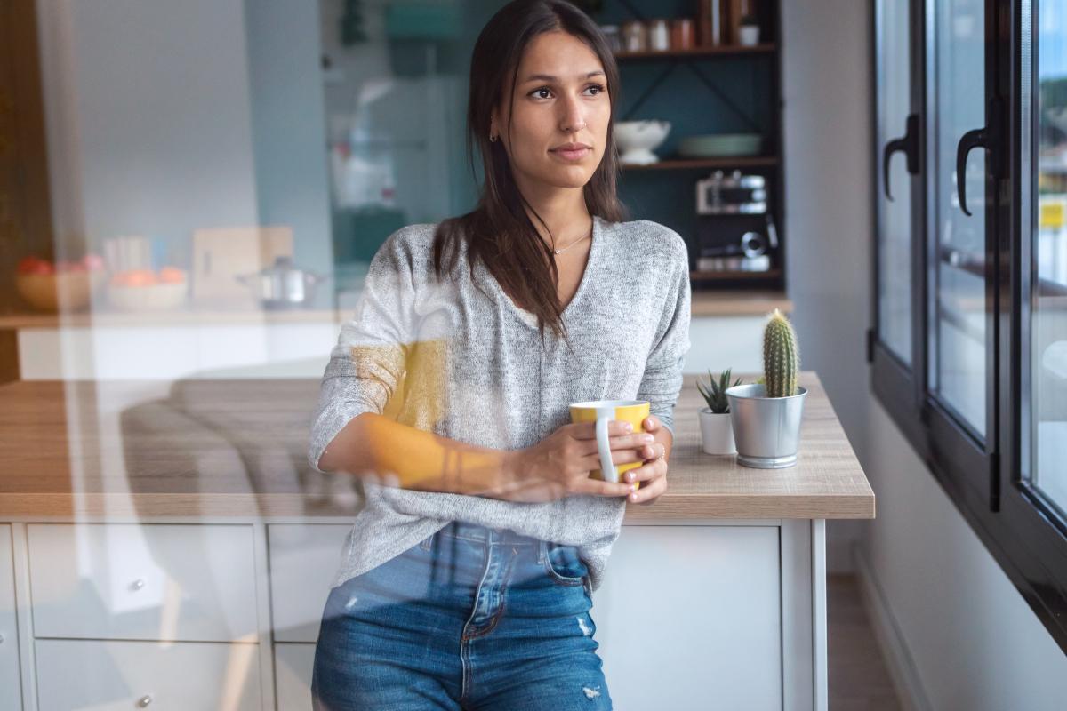 Kobieta pije kawę i patrzy przez okno