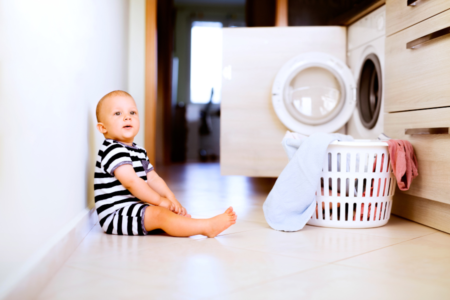 Małe dziecko siedzi obok pralki